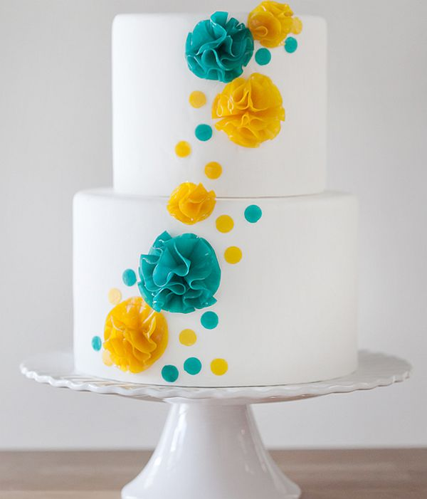 Fruit leather flowers on wedding cake in blue and yellow