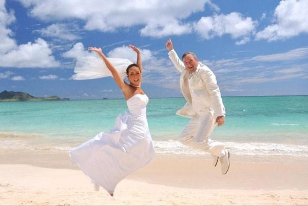 bride and groom jumping with joy on the beach in Oahu, Hawaii