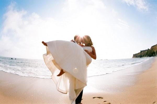 Groom holding bride wearing white wedding dress, kissing on Florida beach