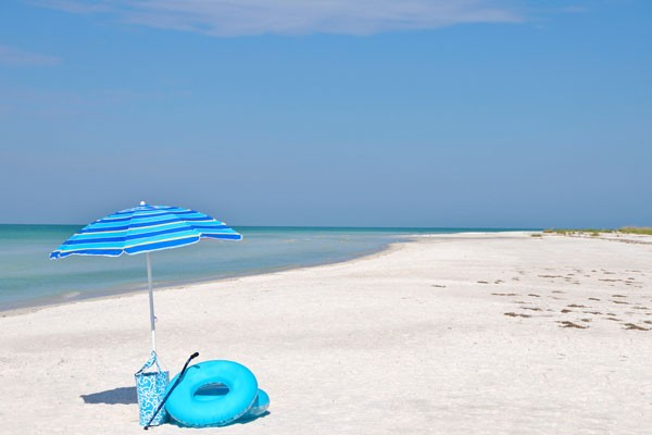 beach on anna Maria Island with a blue striped umbrella