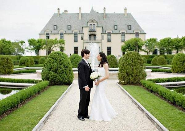 Bride and groom standing in front on mansion in New York