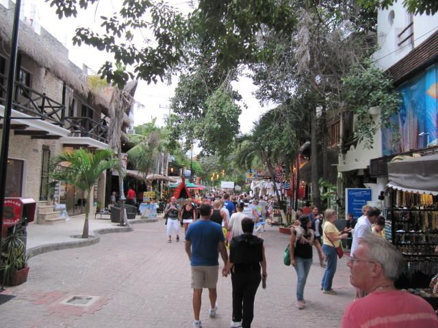 Playa del Carmen busy sidewalk with palm trees