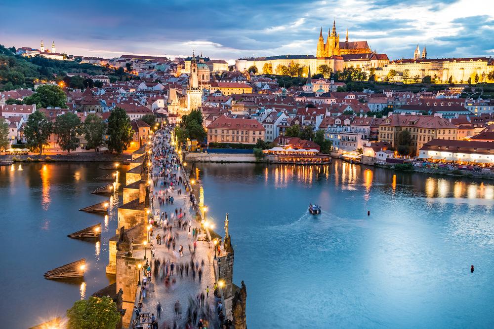 people cross bridge in Prague