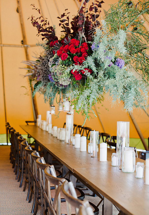 Hanging red floral decor with greenery for long wedding table