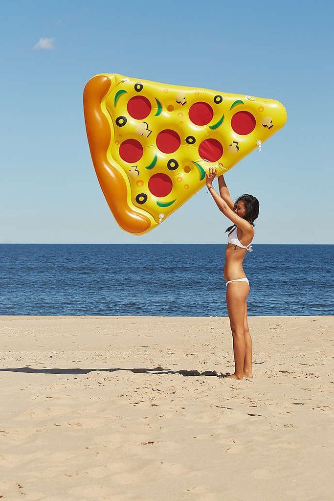 Pool float pizza slice held by girl in swimsuit