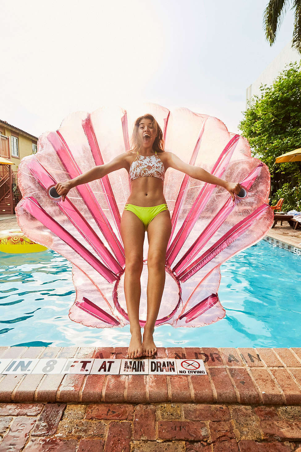 Pool float shell held by girl standing at the deep end