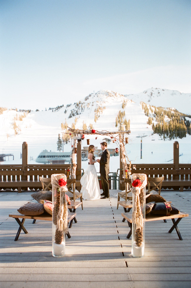 bride and groom under wedding arch outdoors at ski resort