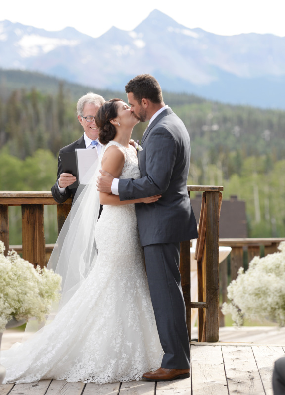 Bride and groom kissing on deck outdoors with mountains in background