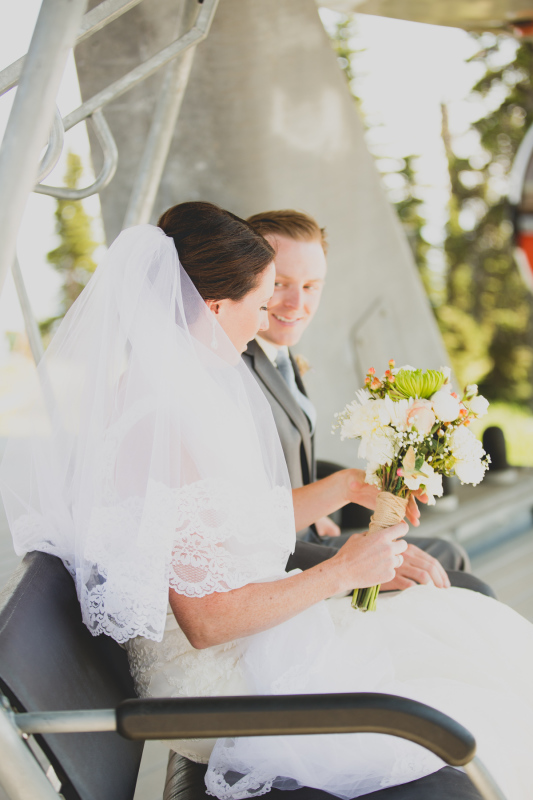 Bride and groom sitting outside with floral bouquet