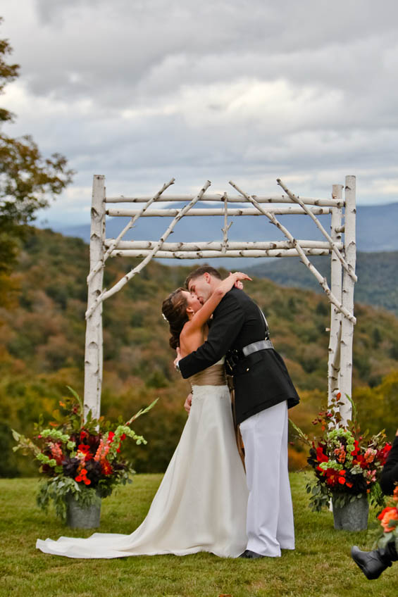 Outdoor wedding couple kissing between wood arch